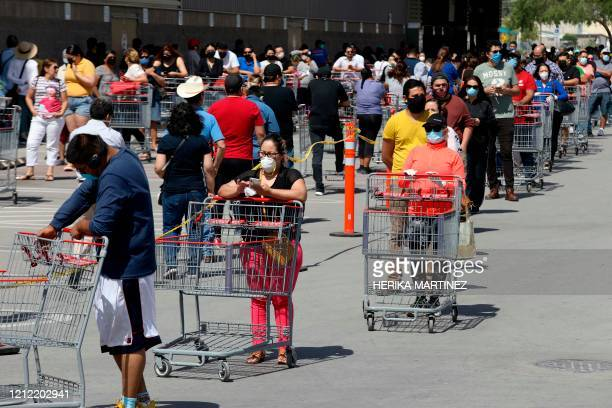 People queue outside a wholesale store respecting the safe social distance as a measure to prevent the spread of the new coronavirus COVID19 in...