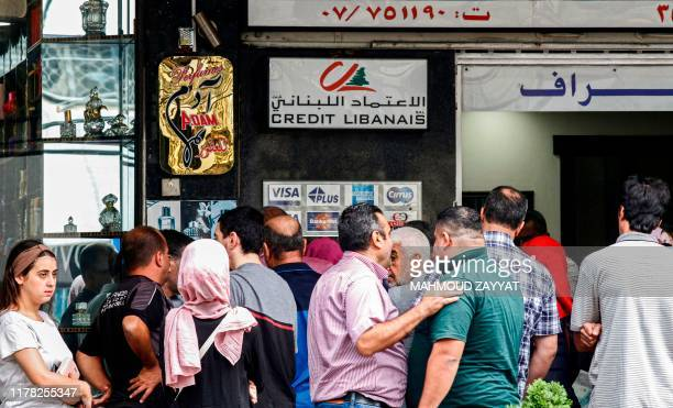 People queue outside an automatic teller machine at a bank in the southern Lebanese city of Sidon on October 26 on the tenth day of countrywide...