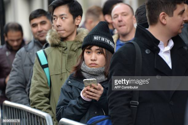 People queue outside Apple's Regent Street store in central London on November 3 2017 waiting for the store to open on the say of the launch of the...