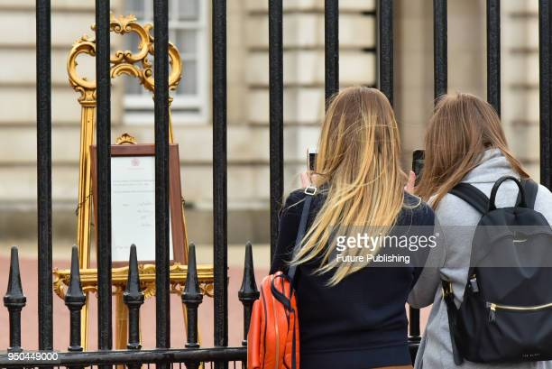 People queue outside Buckingham Palace to see the notice of the announcement of the birth of a baby boy the third child of The Duchess of Cambridge...