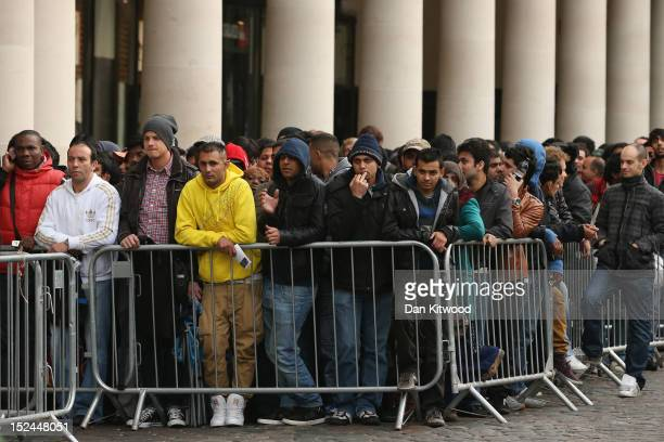 People queue outside the Apple store in Covent Garden to purchase the iPhone 5 smartphone on September 21 2012 in London England The much anticipated...