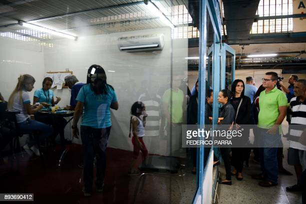 People queue outside the BanPanal communal bank to exchange bolivares for the new local community currency the panal launched in the '23 de Enero'...