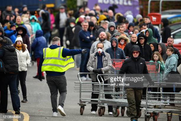 People queue outside the Costco wholesalers on March 21 2020 in Glasgow Scotland Coronavirus has spread to at least 182 countries claiming over 10000...
