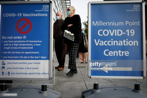 People queue outside the mass NHS Covid-19 vaccine centre that has been set up at the Millennium Point centre in Birmingham on January 11, 2021 in...