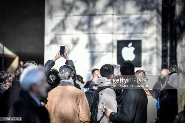People queue outside the new Apple store on its opening day on the Champs Elysees Avenue in Paris on November 18 2017
