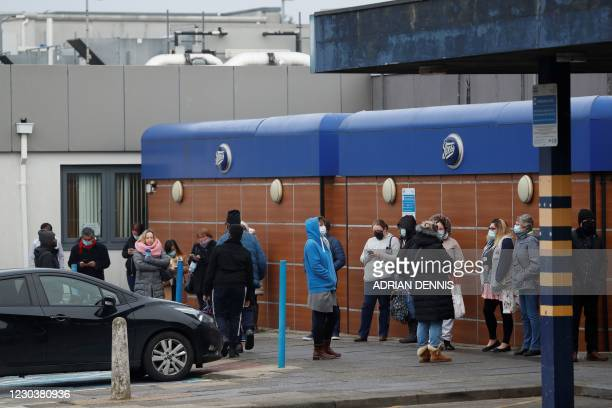 People queue outside the Outpatients Department at the Basildon and Thurrock hospital in south west Essex, eastern England, on January 1, 2021. -...