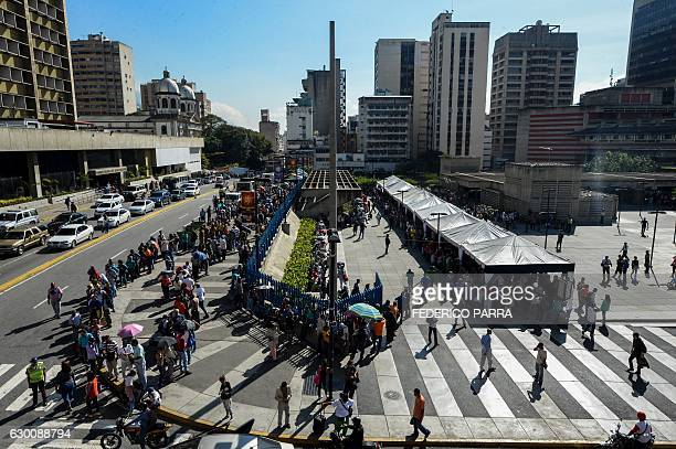 People queue outside Venezuela's Central Bank in Caracas in an attempt to change 100 Bolivar notes on December 16 2016 Venezuelans lined up to...