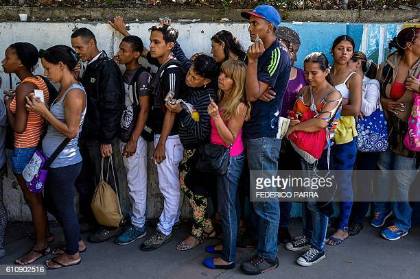 People queue to buy basic food and household items outside a supermarket in Caracas on September 28 2016 Venezuela is in a highly tense political...
