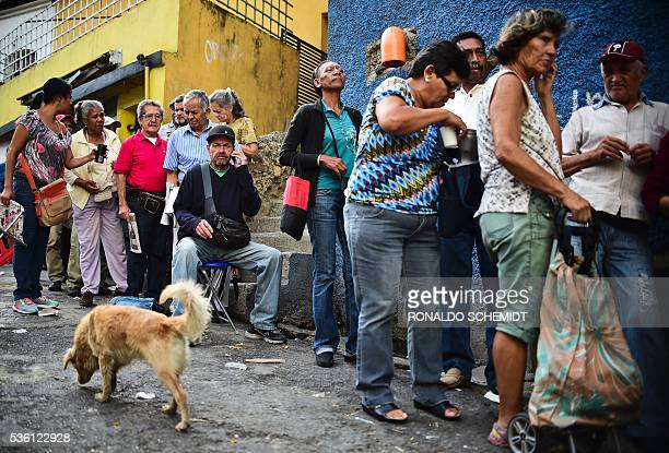 People queue to buy basic food and household items outside a supermarket in the poor neighbourhood of Lidice in Caracas Venezuela on May 31 2016 The...