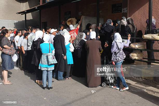 People queue to buy bread, in the back streets of Bab Tuma, on May 29, 2012 in Damascus, Syria. There is shortage of bread, domestic gas, petrol in...