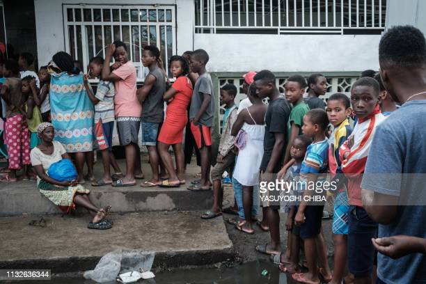 People queue to buy breads in Beira Mozambique on March 24 2019 Cyclone Idai smashed into Mozambique's coast unleashing hurricaneforce wind and rain...