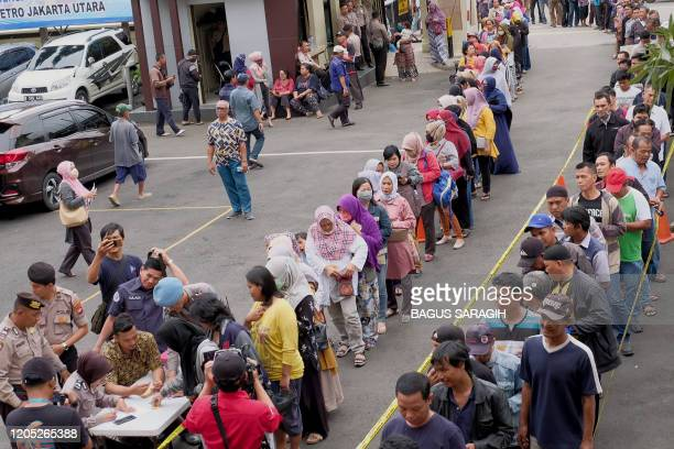 People queue to buy face masks for a lower price following a police press conference on seized face masks at the North Jakarta police headquarters in...