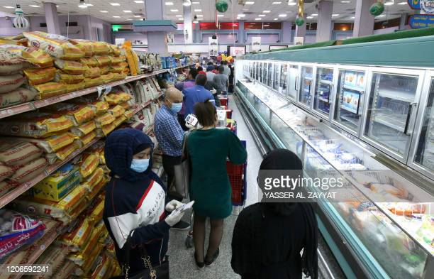 People queue to buy food supplies at a supermarket in Kuwait City on March 11, 2020. - Kuwait announced the suspension of all commercial flights...
