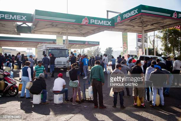 People queue to buy gasoline at a station in Morelia Michoacan State on January 7 2019 as shortages have also been reported in several other Mexican...