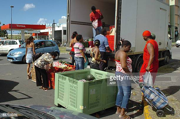 People queue to buy some fruits in a truck parked on the parking of a closed supermarket in Abymes city on February 7 2009 during a strike against...