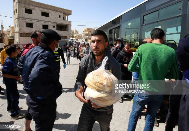 People queue to buy subsidised bread from a municipal bus in the Marka suburb in the east of Jordan's capital Amman on March 24 as the kingdom...