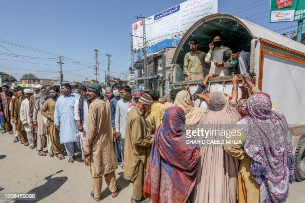 People queue to buy wheat bags at a government food distribution point during a government-imposed nationwide lockdown as a preventive measure...