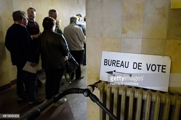 People queue to cast their ballot during a referendum on May 18, 2014 in Bulle, western Switzerland. Swiss voters are to decide whether to bring in...
