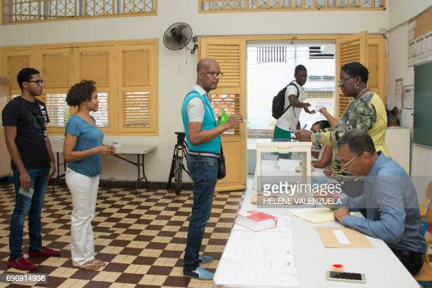 People queue to cast their ballot during the secound round of the French legislative elections at the polling station number 1 in PointeaPitre on...