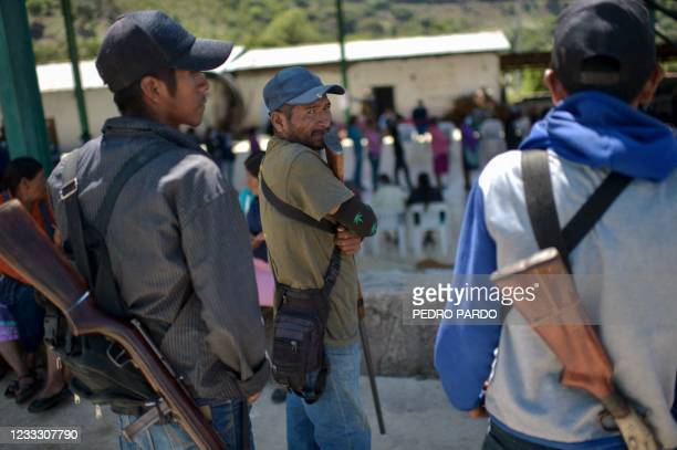 People queue to cast their votes while community policing stand guard at a polling station in Nahuat community of Ayahualtempa, Guerrero state,...