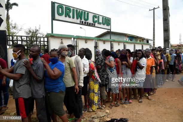 People queue to collect food parcels distributed to cushion the effect of lockdown in the Ikorodu district of Lagos on April 30 2020 President...