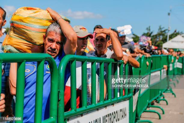People queue to cross the Simon Bolivar international bridge from San Antonio del Tachira in Venezuela to Cucuta in Colombia to buy goods due to...