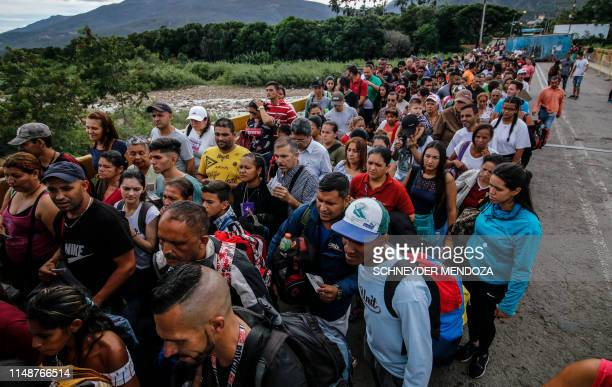 People queue to cross the Simon Bolivar international bridge from San Antonio del Tachira in Venezuela, to Cucuta, in Colombia on June 9, 2019. -...