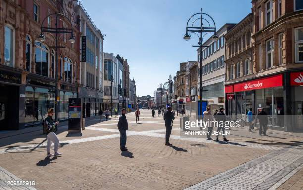 People queue to enter a bank on Briggate in Leeds city centre West Yorkshire on April 14 as life in Britain continues during the nationwide lockdown...