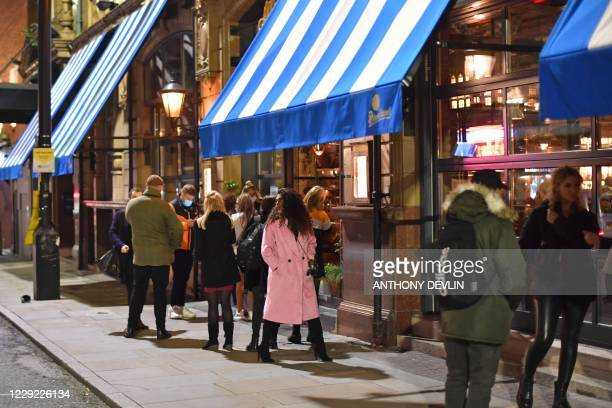 People queue to enter a bar on Peter Street in Manchester city centre northwest England on October 22 2020 ahead of new coronavirus restrictions...