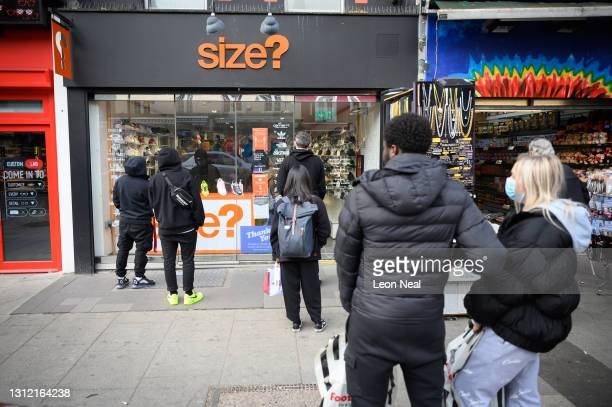 People queue to enter a shoe store after it re-opened following the change in lockdown restrictions on April 12, 2021 in London, United Kingdom....