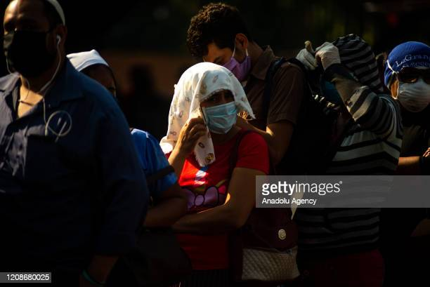 People queue to enter an aid center destined by the Salvadoran government to receive aid of $300 for the purchase of food during the outbreak of the...