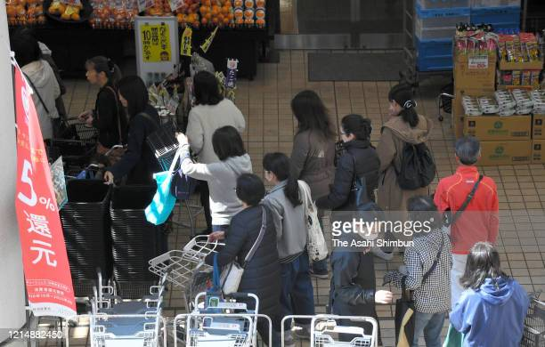 People queue to enter before the opening at a supermarket a day after Tokyo Metropolitan Governor Yuriko Koike urged to stay home on weekend amid the...