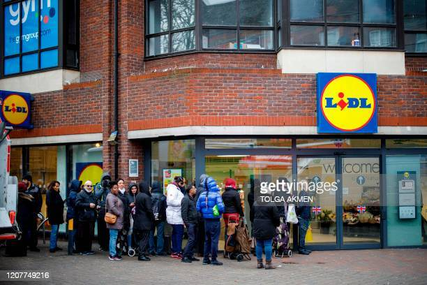 People queue to enter Lidl supermarket before opening in Walthamstow, east London on March 20, 2020. - The British prime minister urged people in his...