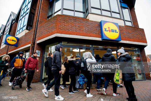 People queue to enter Lidl supermarket in Walthamstow, east London on March 20, 2020. - The British prime minister urged people in his daily press...