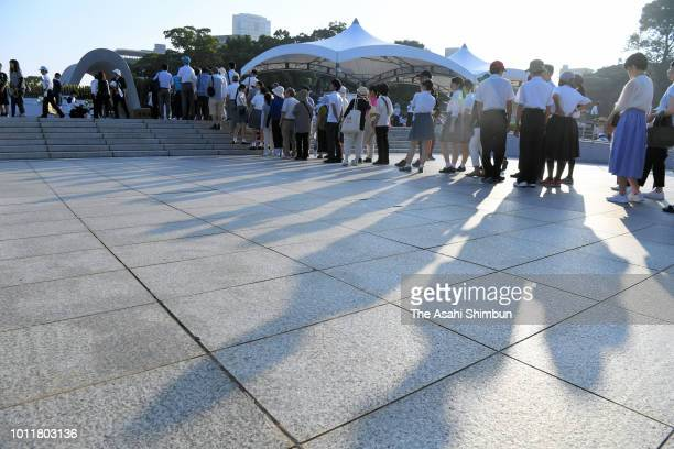 People queue to pray for the victims at the cenotaph prior to the Peace Memorial Ceremony at Hiroshima Peace Memorial Park on the 73rd anniversary of...