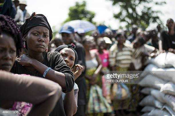 People queue to receive aid near a camp for internally displaced persons in Bangui on December 13 2013 Aid workers warned of a looming humanitarian...