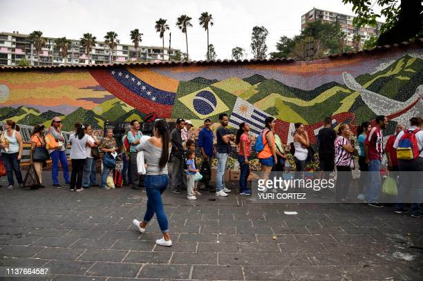 People queue to receive drums to collect water and water purification tablets from members of the Venezuelan Red Cross in Catia neighborhood in...