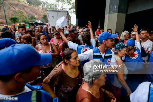 People queue to receive drums to collect water and water purification tablets from members of the Venezuelan Red Cross in Caricuao neighborhood in...