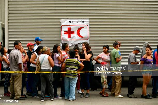 TOPSHOT People queue to receive drums to collect water and water purification tablets from members of the Venezuelan Red Cross in Caricuao...