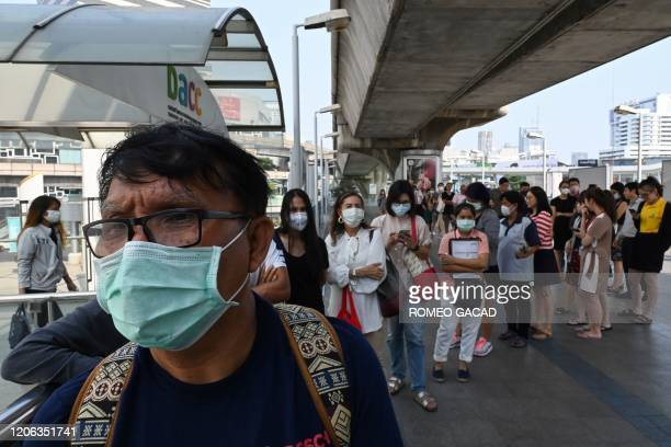People queue to receive free facemasks and alcohol hand gel distributed amid concerns over the spread of the COVID19 novel coronavirus at a train...