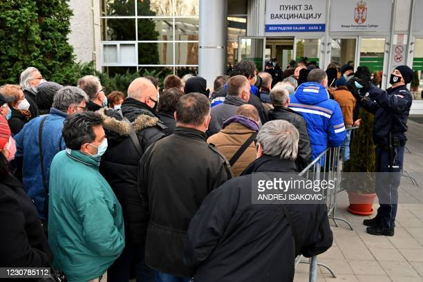 People queue to receive the Chinese-made Sinopharm Covid-19 vaccine, outside the Belgrade Fair turned into a vaccination centre, on January 25, 2021....