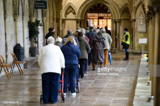 People queue to receive the Pfizer Covid vaccine at the vaccination centre set up inside the Cathedral on January 20, 2021 in Salisbury, England....