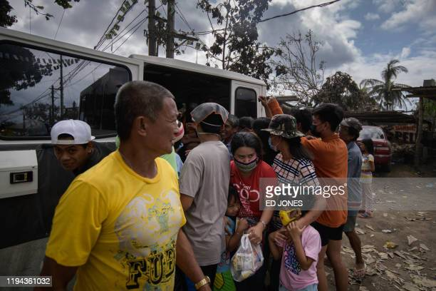 People queue to recieve private aid donated for villages affected by the Taal volcano eruption near Tagaytay on Janaury 18 2020