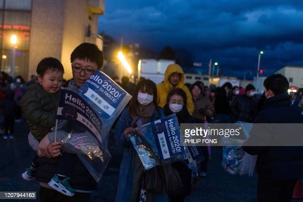 People queue to see the Tokyo 2020 Olympic flame on display outside the railway station in Hanamaki, Iwate prefecture on March 22, 2020. - The flame...