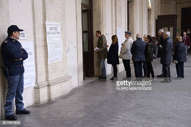 People queue to vote during a referendum on constitutional reforms on December 4 2016 outside a polling station in Rome Italians began voting today...