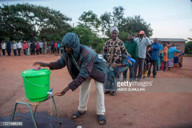People queue to wash their handsas a preventive measure against the spread of the COVID-19 coronavirus before they can queue again to vote at the...