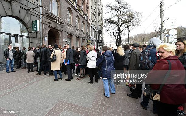 People queue to withdraw cash money at an ATM of the Khreshchatyk Bank in Kiev on April 5 2016 TheNational Bank of Ukraine recognised on April 5 2016...