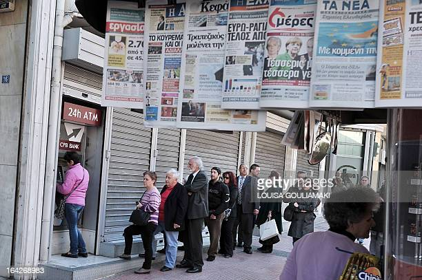 People queue to withdraw their savings at a Cypus Popular Bank ATM in Athens on March 22 while newspapers bear titles about the Cypriot crisis The...