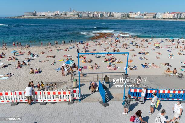 People queue up at beach capacity control measures before being allowed to enter Riazor beach on July 7 2020 in A Coruna Spain Since June 22 to enter...