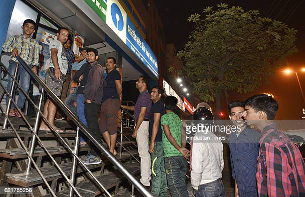 People queue up outside ATMs to withdraw hundred rupee notes at Defence Colony market on November 8 2016 in New Delhi India Prime Minister Narendra...